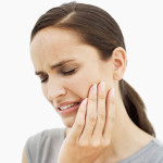 歯を押さえる外国人女性